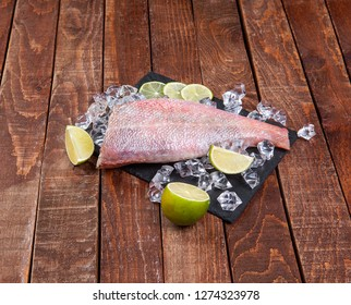 Sea perch on a black board. sea ​​bass on a black board with ice and lime. Fish on the table. ocean perch