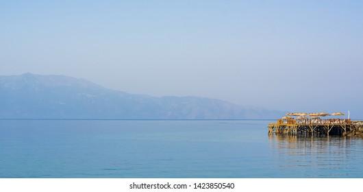 Sea, pier and umbrellas, Assos, Canakkale, Turkey