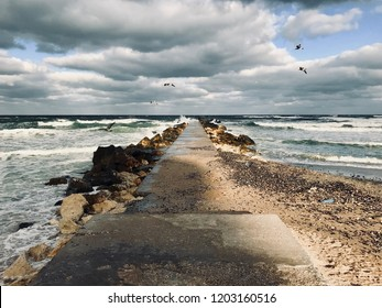 Sea pier/concrete and stones pier into the waves of the Black Sea with seagulls above on a sunny autumn windy day.