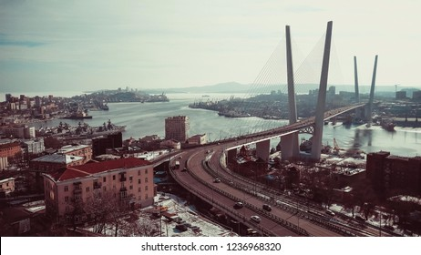 Sea port, harbor, cityscape. In the foreground is a modern road bridge. Away city buildings. In the bay on the roads are ships. Cold winter day. Bright sky, copy space. Vintage style.