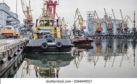 Sea port. Tug, floating crane, dry cargo ship and other infrastructure of the port.