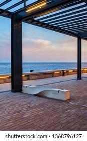Sea promenade at dusk with pergola and bench in Monaco, Europe