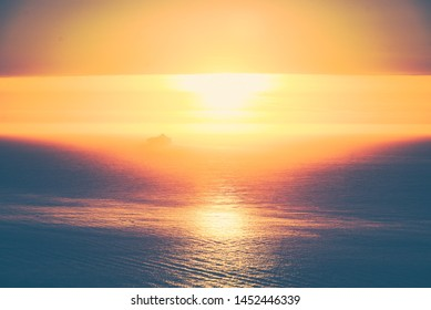 A sea reflecting the sun at sunset in Presidio of San Francisco with a ship in the distance