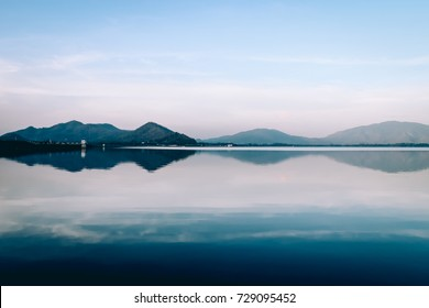 sea and reflection of mountain in calm morning
