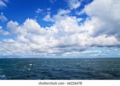 Sea ripples under cloudy sky; sea shore on horizon