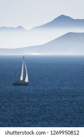 sea with sailboat and mountains of an island in haze, concept for travel, watersports and vacation, Lanzarote, canary islands, Spain, Europe
