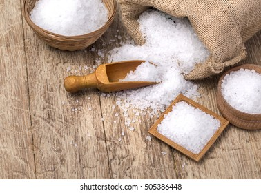sea salt in the bag and with wooden spoon on wooden background