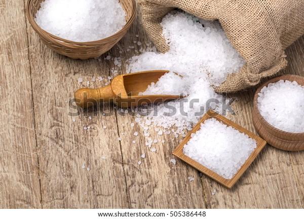mořská sůl v sáčku a dřevěnou lžící na dřevěném pozadí
