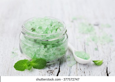 Sea salt bath scented mint for spa and aromatherapy on white wooden background, rustic style