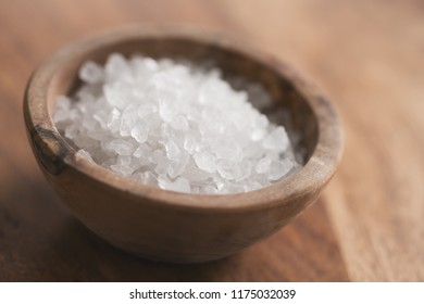 Sea salt in bowl on wood table