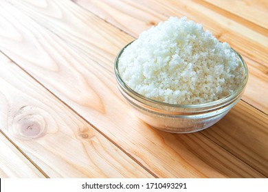 Sea salt in bowl on wooden background, Sea salt is salt that is produced by the evaporation of seawater. Used as a seasoning in foods, cooking, cosmetics and for preserving food.
