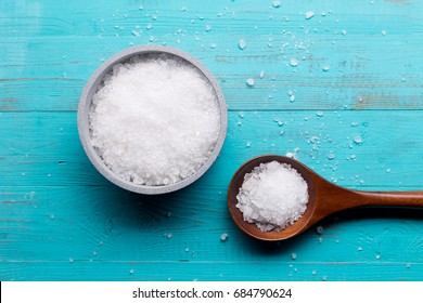 sea salt in bowl and in spoon on wooden background