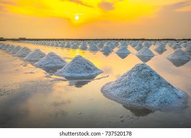 Sea salt evaporation pond with golden sunset sky background in Petchaburi, Thailand. Closeup of sea salt pile pyramid. Sea salt farming concept.