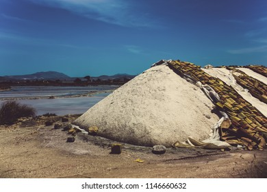 Sea salt evaporation pond in  in Salemi near Marsala, Sicily. Closeup of sea salt pile pyramid. Sea salt farming concept