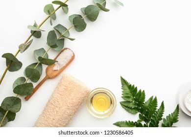 Sea salt, loofah and eucalyptus essential oil on white background