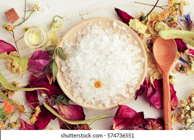 Sea salt mineral grains on round wooden plate dried petals medicinal plants. Herbal aroma bath salt blend. toned