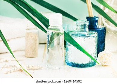 Sea salt mineral rich skin care spray, spa treatment facial toner. Blue glass jars, sea salt, palm leaves & towels, blue fresh toned.
