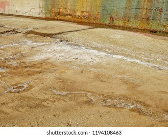 Sea salt on the floor of a dry dock for large ships. On the reinforced concrete wall, sea water with green algae and rust.