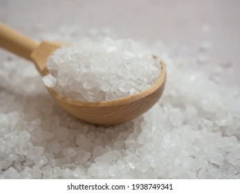 sea salt, a pile of sea salt in a wooden spoon on a light concrete background