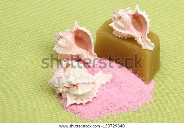 Sea salt, sea shell and handmade soap composition on green background