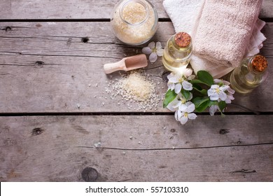 Sea salt, towels, aroma oil in bottles and flowers on  vintage  wooden background. Selective focus. Flat lay with copy space.