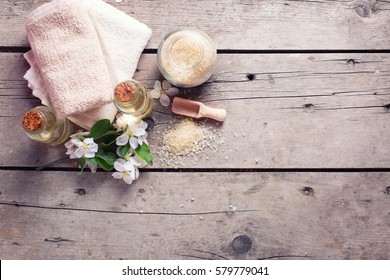 Sea salt, towels, aroma oil in bottles and flowers on wooden background. Selective focus. Flat lay  with copy space.