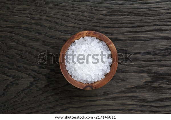 sea salt in wooden bowl for cooking or spa, on dark oak table