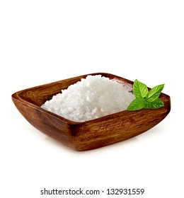 Sea salt in wooden plate with fresh mint on white background
