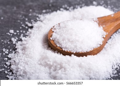 sea salt in a wooden spoon on dark table.