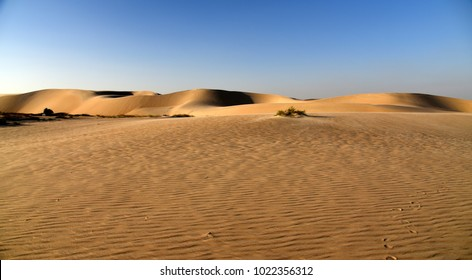 A Sea of Sand Leading to the Dunes and Blue Sky of the Arabian Desert