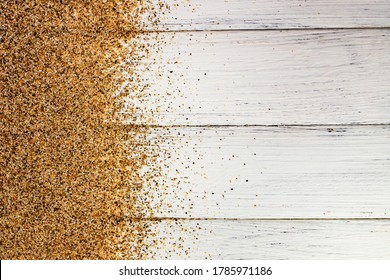 Sea sand scattered on a white wooden background. Abstract background for design. Flat lay. Place for text.