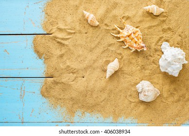 Sea sand and shells on wooden table. Top view with copy space