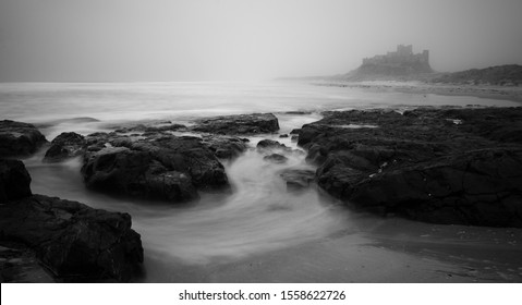 Sea scape of swirling sea under a foggy bamburgh castle in black and white