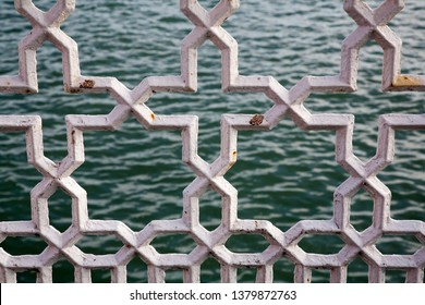 the sea seen through white painted metal in a stars and cross pattern showing a little rust on an edwardian seaside pier