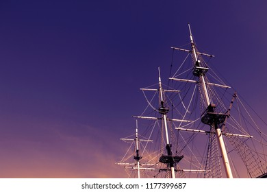 Sea ship masts and ropes against purple sunset sky. Concept of travel, adventure and sea. Copy space.