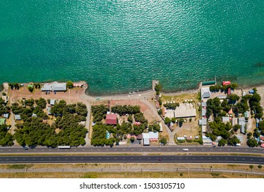 Sea shore from aerial view. Resort town. Blue water. Highway and railroad near sand beach. Tourism and vacation