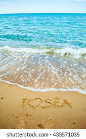 Sea shore and beach with yellow sand with sign I love sea