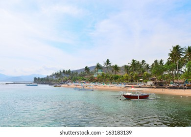 Sea shore on Bali in Candidasa with traditional wooden fishing boats on a beach