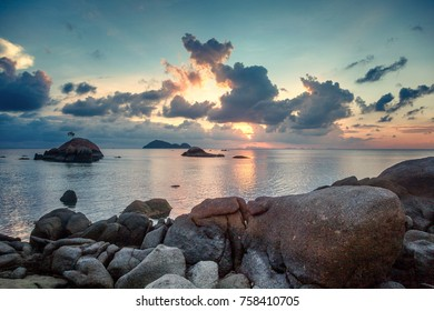 Sea shore at sunset with large stones and reflection of clouds in the water. Beautiful tropical landscape