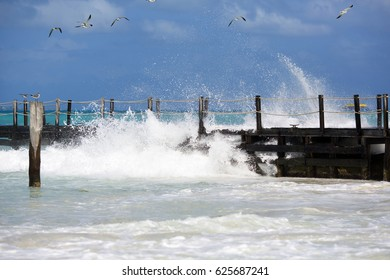 Sea is showing it's power. A huge wave is hitting hard on the harbor. Long wooden bridge is getting the waves.