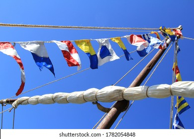 Sea signal flags mounted on the mast against the blue sky, taken close-up. Ship's flags fluttering in the sky. Signals, Morse code. Flagpole.