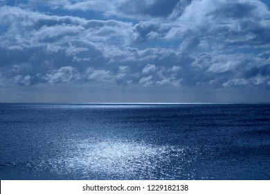 Sea and sky in the bottom half is a calm deep blue sea, on the horizon is a line of white shimmering glowing light from the moon in the upper half is the sky covered in fluffy clouds