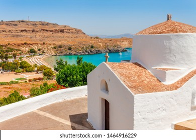Sea skyview landscape photo bay and orthodox church in Lindos on Rhodes island, Dodecanese, Greece. Panorama with nice sand beach and clear blue water. Famous tourist destination in South Europe
