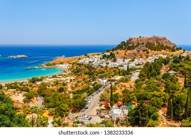 Sea skyview landscape photo Lindos bay and castle on Rhodes island, Dodecanese, Greece. Panorama with ancient castle and clear blue water. Famous tourist destination in South Europe