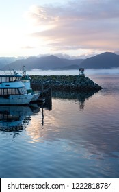 Sea smoke on sunrise of Sitka Alaska harbor, piers with docked boats. clouds and pink sky reflecting on pacific ocean