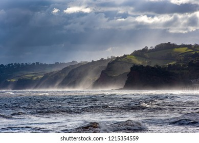 Sea spray highlighted by backlighting. Teignmouth, Devon, UK and the coast southwards towards Torbay.