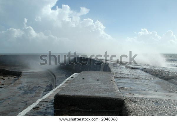 Sea spray over harbor wall