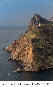 Sea spring landscape. Picturesque mountains and the sea with a boat against the  blue sky. Rocks and green hills.  Crimea, Balaklava