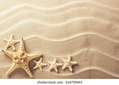 Sea star fish on an idyllic tropical beach with ripples in the sand. Tree starfish as concept for summer holiday or vacation, texture background with copy space.