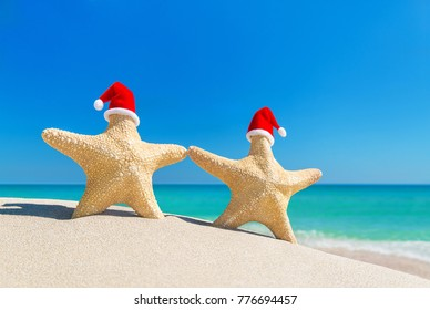 Sea stars couple (starfishes) in red Santa hats at ocean sandy beach. Happy New Year and Merry Christmas tropical vacation and greeting cards concept.
